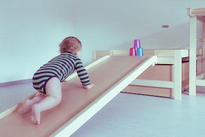 Ergotherapie bei Kindern: Kleinkind krabbelt die Rollbrettbahn hinauf