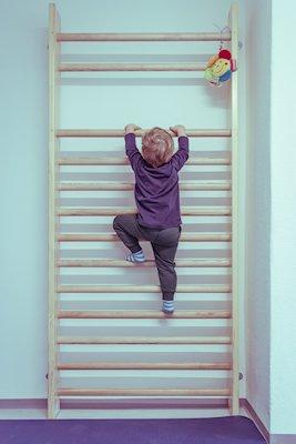 Ergotherapie bei Kindern: Kleinkind klettert die Sprossenwand hinauf